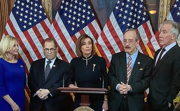 La presidente de la Cámara de Representantes, Nancy Pelosi flanqueada por un grupo de correligionarios demócratas haciendo uso de oa palabra para anunciar las acusaciones al presidente Trump.