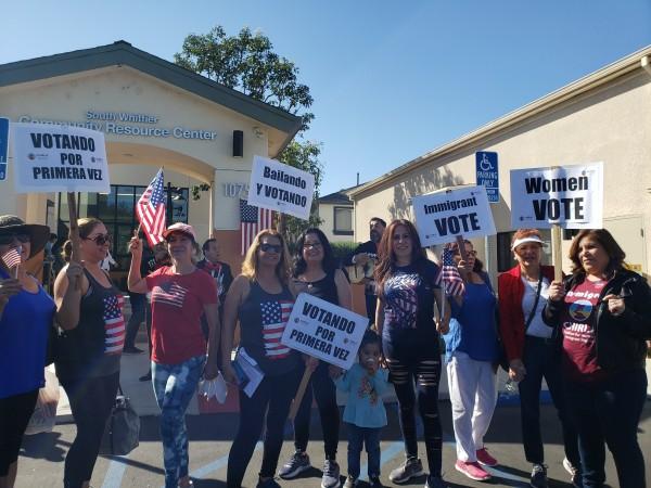 En la calle un grupo de personas a punto de depositar su voto.