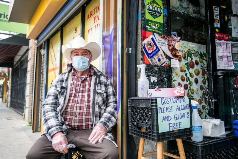 Santiago Briseño asegura que todos los clientes usen guantes y que los guantes estén desinfectados cuando ingresen a Mi Ranchito Market, en Foothill Blvd, Oakland, CA, 8 de abril de 2020. Foto: Beth LaBerge / KQED.