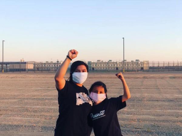 Dos generaciones de activistas de Puente, Arizona, posan frente a penal privado para migrantes, La Palma.