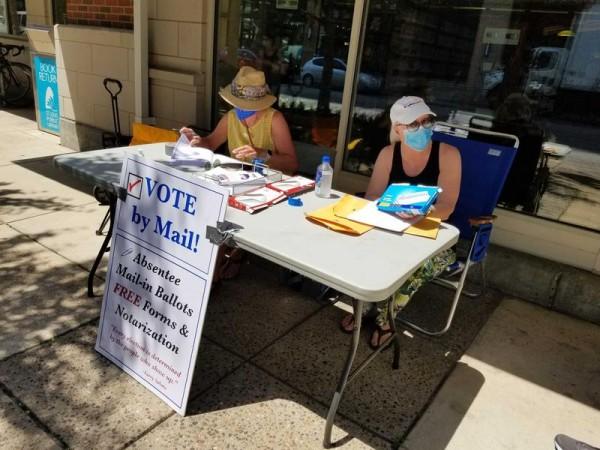 Organizadores ayudan a las personas que desean votar en ausencia fuera de la sucursal de Schlafly de la Biblioteca Pública de St. Louis en el West End central. Foto: https://news.stlpublicradio.org.