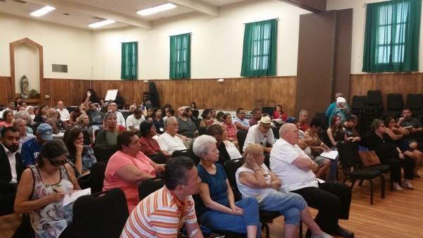 En salón de la Iglesia Resurrección. Residentes afectados por la contaminación de plomo escuchan cómo va la limpieza de su barrio.