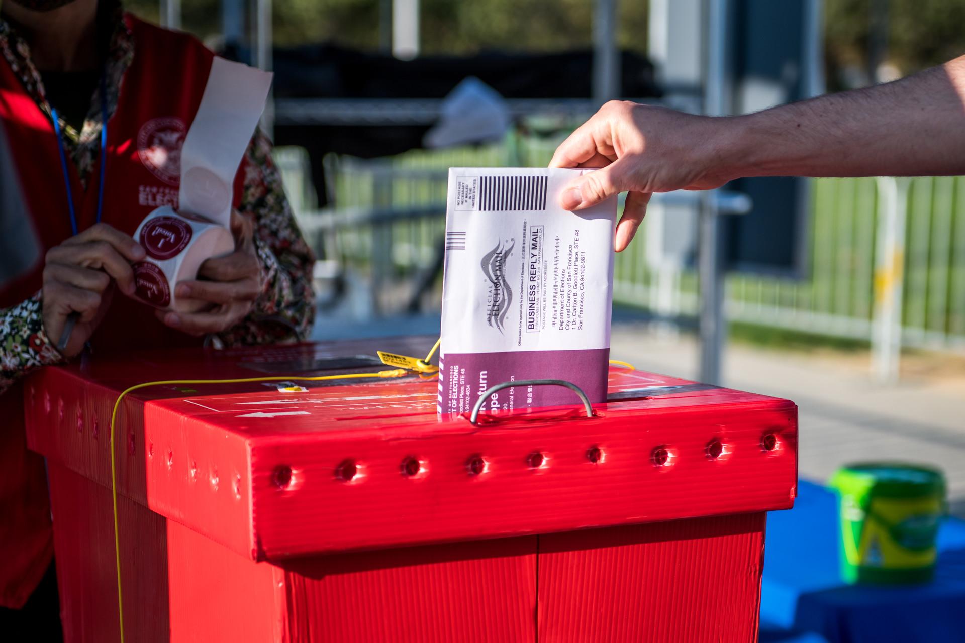 Un votante deja una boleta en un nuevo centro de votación al aire libre cerca de Civic Center Plaza en San Francisco el 5 de octubre de 2020, el primer día de votación anticipada. Foto: Beth LaBerge / KQED.