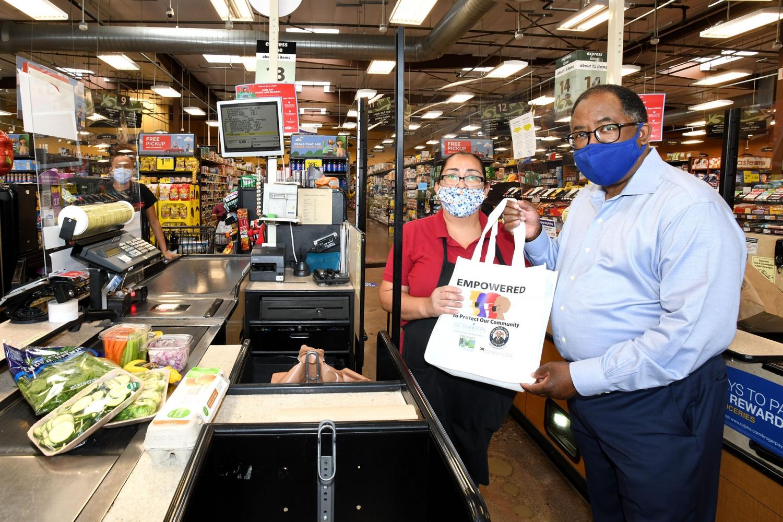 El supervisor Mark Ridley-Thomas le da a la cajera de un supermercado Ralphs una bolsa de regalo que contiene máscaras gratis. Foto: Aurelia Ventura / Junta de Supervisores.