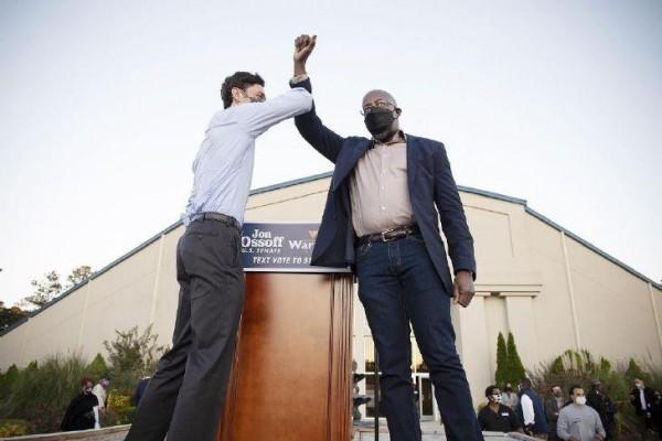 Los candidatos demócratas, Jon Ossoff y el reverendo Raphael Warnock se codean en el escenario en un mitin en Jonesboro, Georgia, el 19 de noviembre de 2020. Foto: https://norwalkreflector.com.