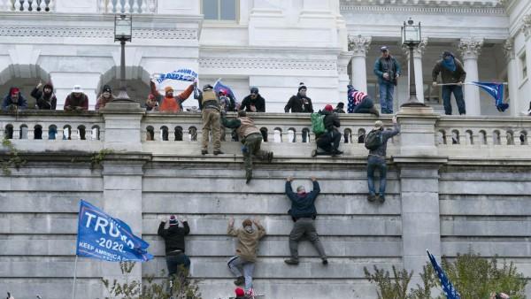 Seguidores de Trump trepando por las paredes del Capitolio para ingresar con violencia en el recinto oficial a protestar el triunfo del presidente Biden. Foto: https://www.ajc.com.