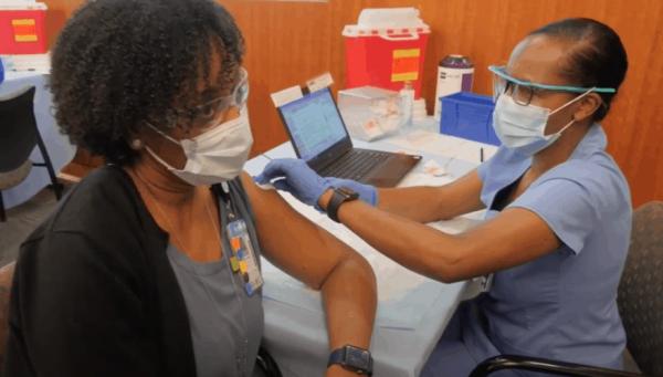 La directora de enfermería de UNC Health, Turkeisha Brown, recibe la vacuna Pfizer COVID-19 de uno de sus compañeros de trabajo el martes por la mañana. Foto: Cortesía de UNC Health.