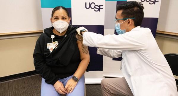 Un asistente de apoyo al paciente en UCSF Hospitality Services, recibe una inyección de COVID-19 el 16 de diciembre, el primer día en que UCSF distribuyó las vacunas a sus trabajadores de primera línea. Foto: Susan Merrell / www.universityofcalifornia.edu.