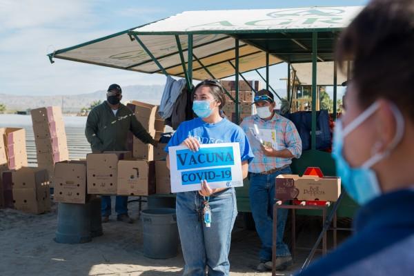 """: Montserrat Gómez, voluntaria de TODEC Legal Center, habla con trabajadores agrícolas sobre la vacuna contra covid-19. """"Están asustados porque no tienen la información correcta""""."""