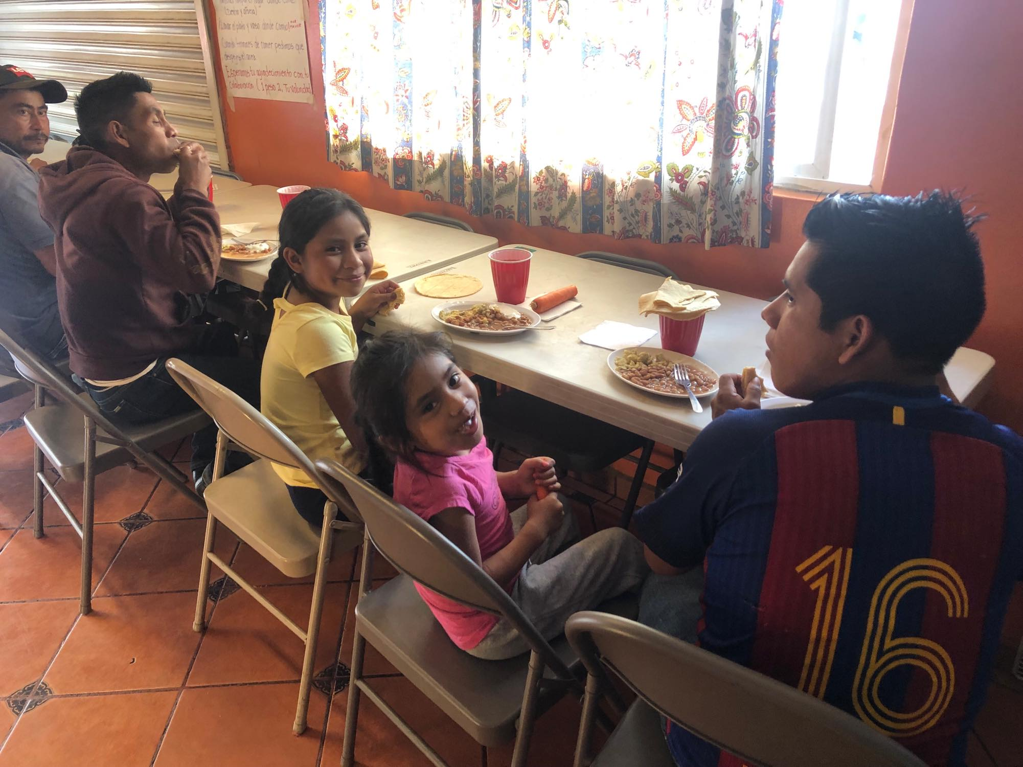 Familia migrantes comiendo en el Comedor comunitario de Contra Viento y Marea en Tijuana, B.C., México. Foto: Devi Machete.