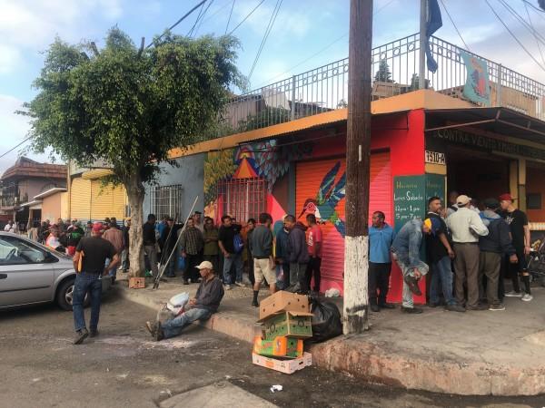 Migrantes y personas vulnerables de la calle en la Zona Norte de Tijuana hacen fila para entrar a comer al Comedor Comunitario de Contra Viento y Marea.