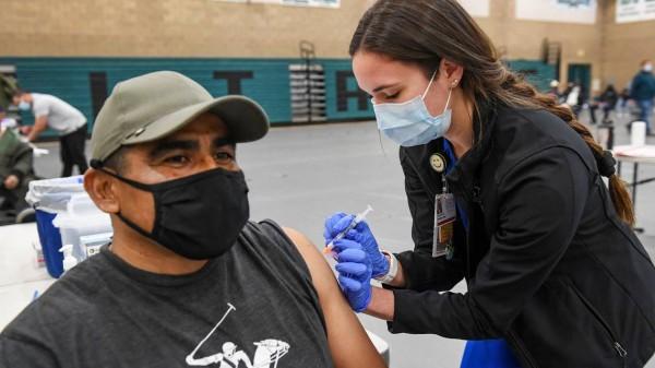 La estudiante de enfermería de Fresno State Monique Lange administra una vacuna COVID-19 Moderna a Ricardo Andrade de Reedley durante una clínica de vacunación rural del condado de Fresno en Orange Cove High School el martes 16 de marzo de 2021. CRAIG KOHLRUSS Archivo de Fresno Bee .