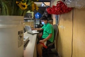 Abraham Osorio se conecta a sus clases en línea desde la florería.