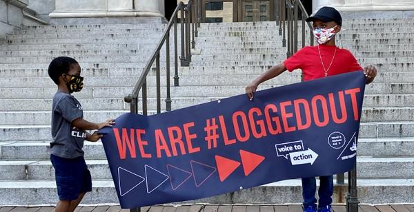 Dos jóvenes sostienen un cartel en el mitin #LoggedOut del Distrito 6 de la Red de Ayuda Mutua / Serve Your City cerca de la Casa Blanca. Foto: Taylor Swaak / The 74.