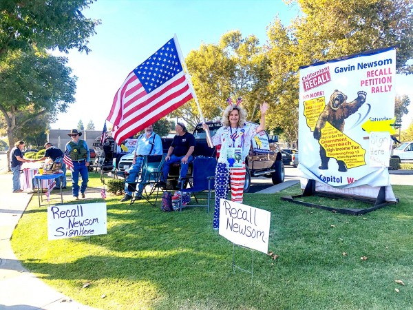 Mujer ondea una bandera estadunidense mientras protesta contra el gobernador Gavin Newsom y recoge firmas para su destitución. Foto: Angelina Martin / https://www.turlockjournal.com.