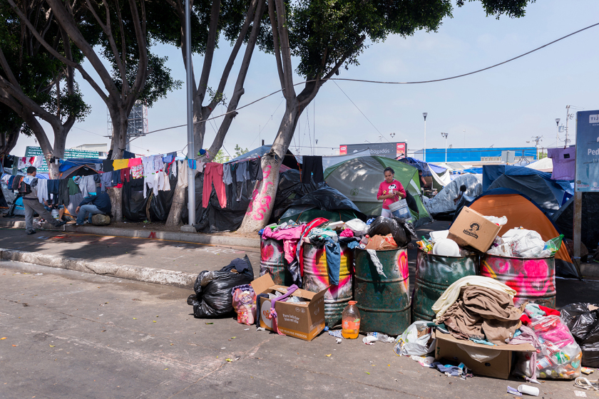 The migrant camp at El Chaparral Plaza overflows with trash and debris. (Heidi de Marco/KHN)